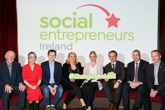 Featured entrepreneurs sitting in a row in front of a social entrepreneurs Ireland sign